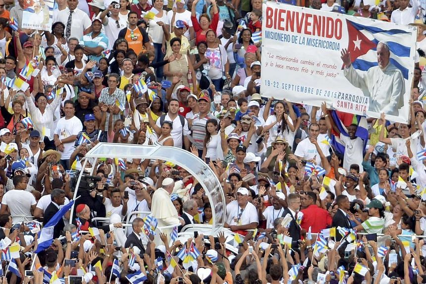 Pope Francis riding past the Catholic faithful (above) in Havana's Revolution Square on Sunday, after holding the first Mass of his visit to Cuba. He also met and discussed religion and world affairs with revolutionary leader Fidel Castro.