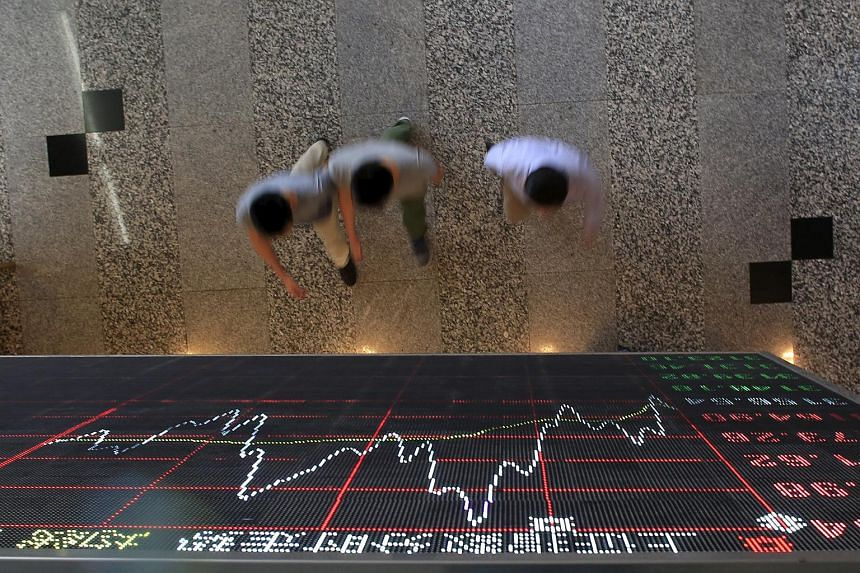 People walking under an electronic board showing stock information at the Shanghai Stock Exchange in Lujiazui Financial Area.