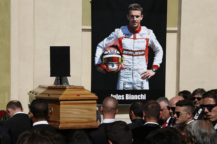 Pallbearers carrying the coffin of French Formula One driver Jules Bianchi past a portrait of him during his funeral ceremony on July 21, 2015.