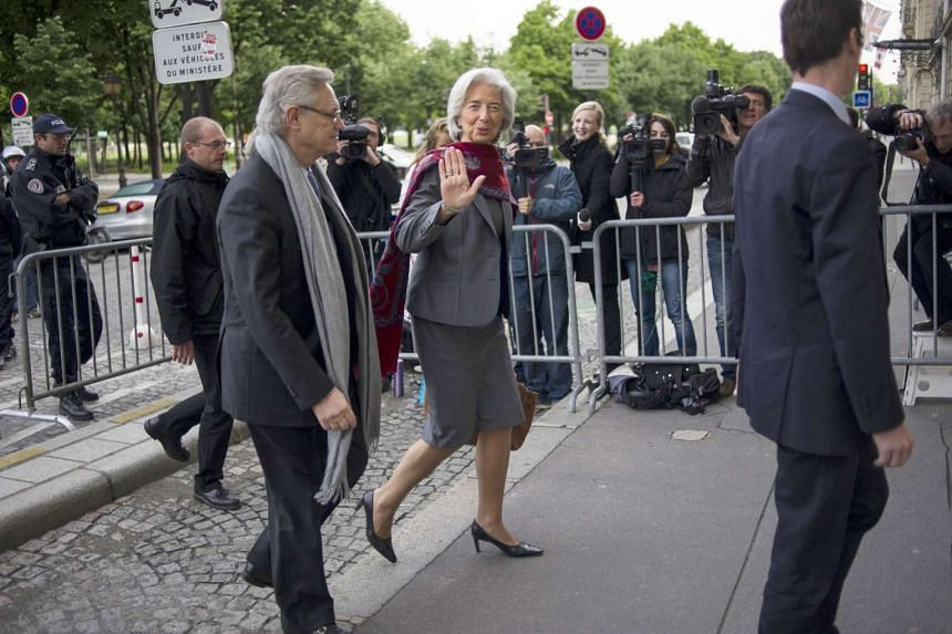 Christine Lagarde (centre), flanked by her lawyer Yves Repiquet (left), arriving at the French Court of Justice in this May 24, 2013 file photo.