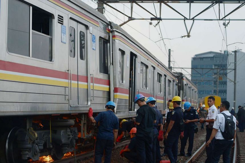 Indonesian workers weld part of a train wagon after a packed commuter train slammed into the back of another at a train station on Sept 23, 2015.