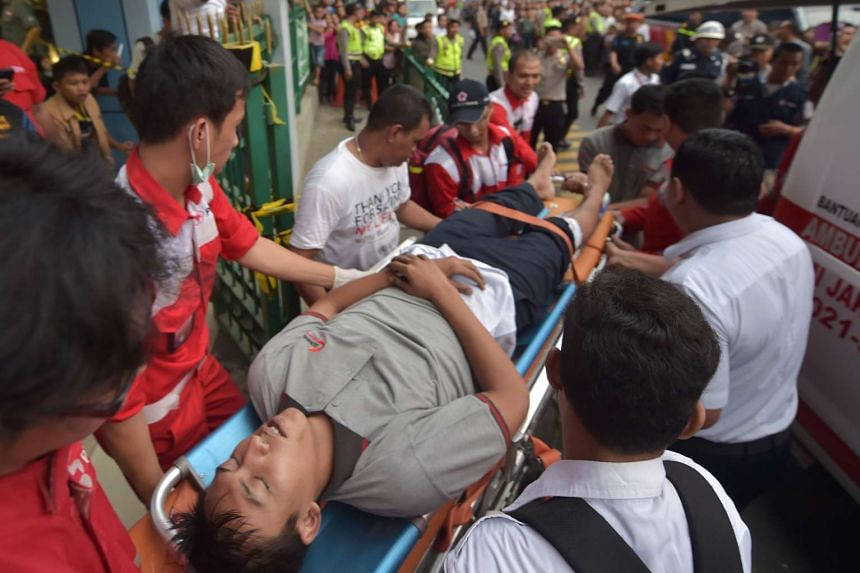 Members of an Indonesian medical team help an injured man after a packed commuter train slammed into the back of another at a train station on Sept 23, 2015.