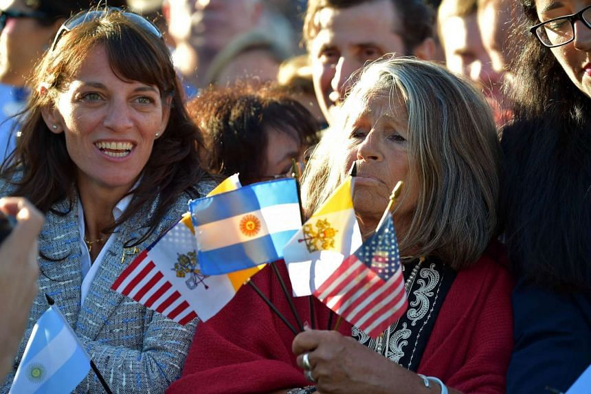 People hold flags as they wait for the arrival of Pope Francis at the White House on September 23, 2015 in Washington,DC.