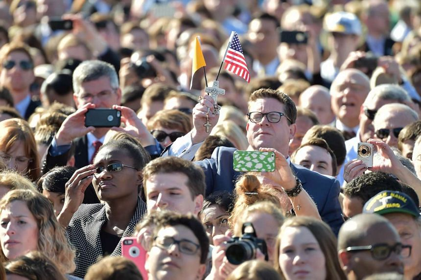 People listen as Pope Francis speaks during an arrival ceromony at the White House on September 23, 2015 in Washington,DC.