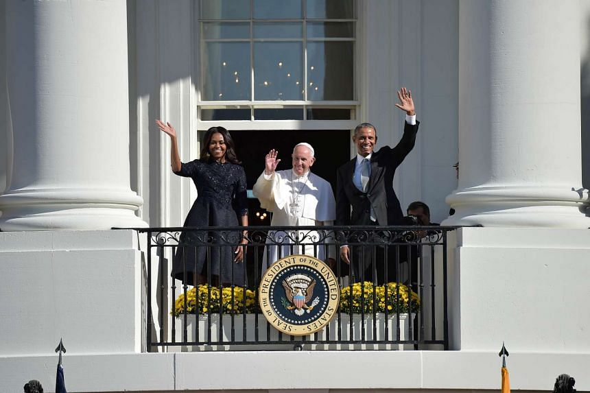 US President Barack Obama, First Lady Michelle Obama and Pope Francis wave during an arrival ceromony at the White House on September 23, 2015 in Washington,DC.