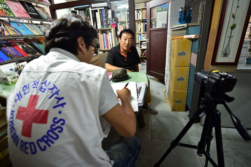 This photograph taken on Sept 9, 2015 shows 70-year-old Kim Ik-Je (centre), one of family members separated by the 1950-53 Korean War, during an interview by a Red Cross official at his book store in Seoul.