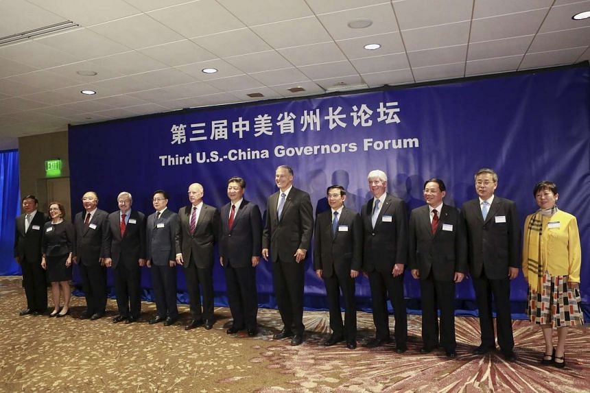Chinese President Xi Jinping (centre) stands with US and Chinese Governors before a forum on the first day of his trip to Seattle, Washington on Sept 22, 2015.