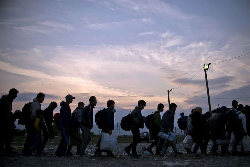 Migrants and refugees queue at a camp to be registered after crossing the Macedonian-Greek border near Gevgelija on Sept 22, 2015