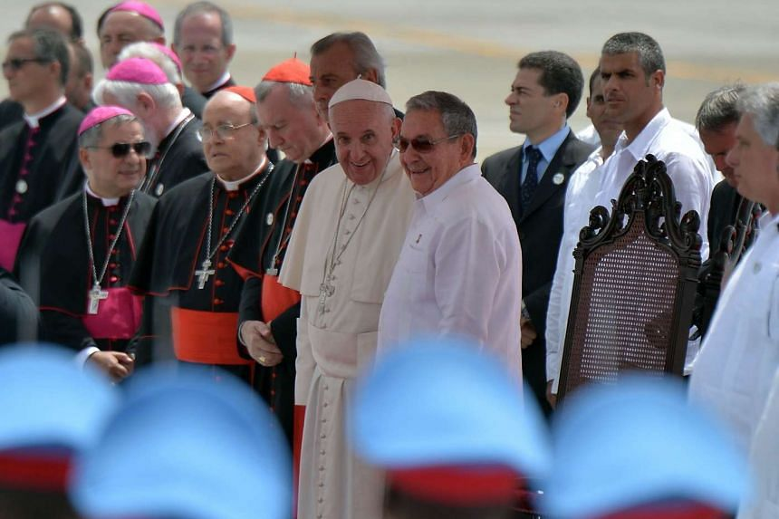 Pope Francis (centre left) chats with Cuban President Raul Castro (centre right) during the farewell ceremony.