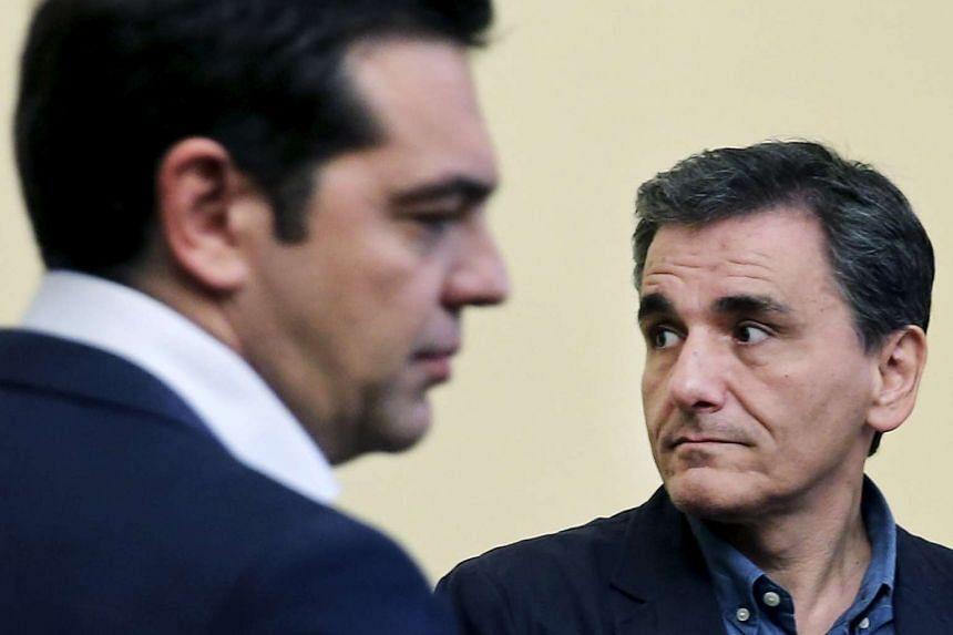 Greek PM Alexis Tsipras (left) gave the crisis-hit country's key finance portfolio to Euclid Tsakalotos (right).