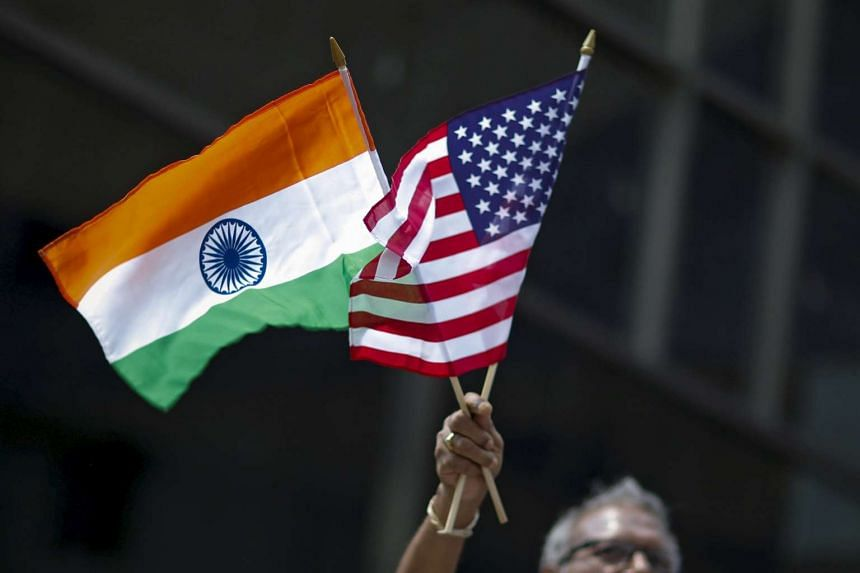 A man holds the flags of India and the US during the 35th India Day Parade in New York on Aug 16, 2015