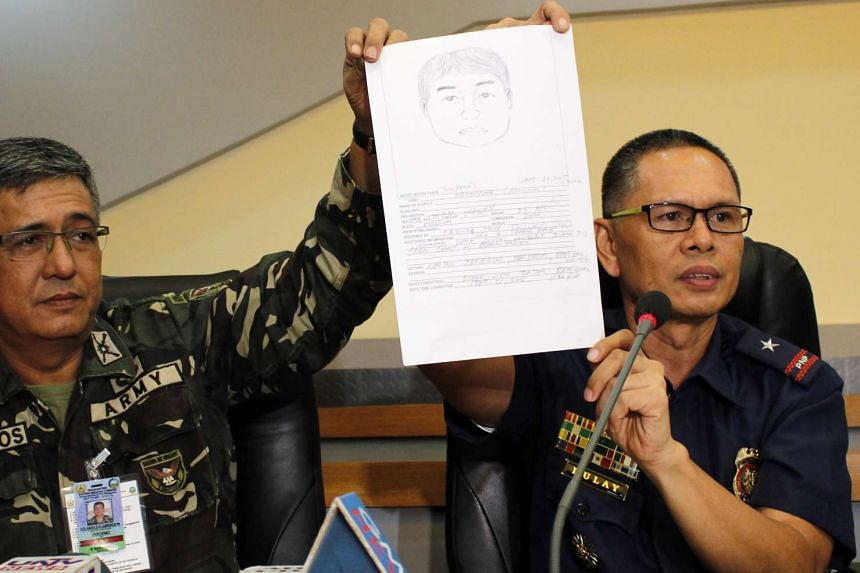 Filipino Army colonel Harold Cabreros (left) with Police colonel Federico Dulay (right) hold a sketch of an unidentified suspect believed to be one of the gunmen who abducted three foreigners and a Philippine woman, during a press conference in Davao