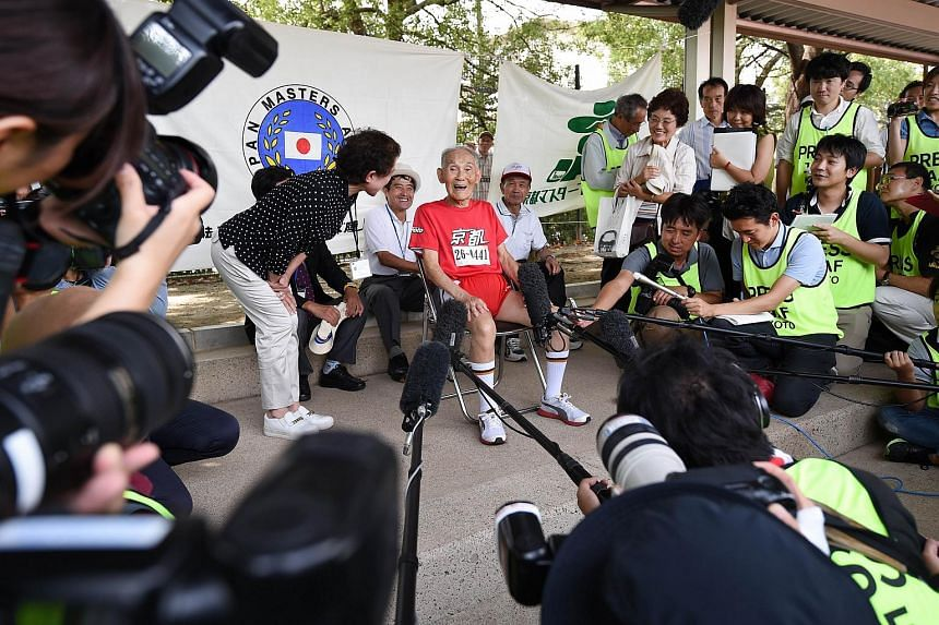 Hidekichi Miyazaki (centre, in red), 105, speaks to the press after running with other competitors over eighty years of age during a 100-metre-dash in the Kyoto Masters Autumn Competiton in Kyoto, western Japan, on September 23, 2015.