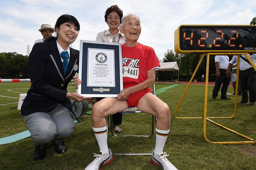 Hidekichi Miyazaki (centre), 105, holds the certificate from the Guinness World Records after running with other competitors over eighty years of age during a 100-metre-dash in the Kyoto Masters Autumn Competiton in Kyoto, western Japan, on Sept 23,