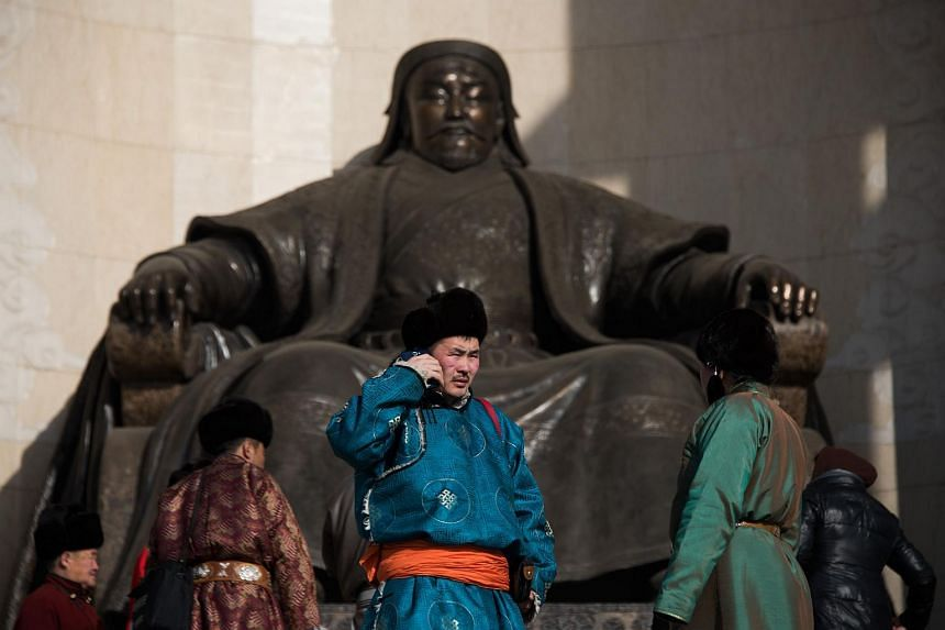 A man stands next to a statue of Kublai Khan in front of the Parliament House on Sukhbaatar Square in Ulan Bator, Mongolia in this Feb 9, 2015 file photo.