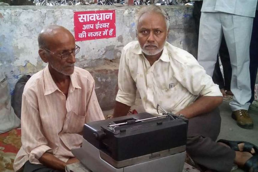 Indian street typist Kishan Kumar (left) with an unidentified man (right) and his new typewriter on a street in Lucknow on September 22, 2015, after he was presented with the new machine following the destruction of his original in a police anti-encr