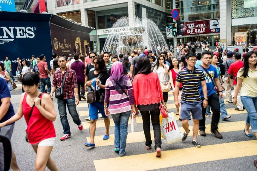 Pedestrians crossing a street outside the Pavilion Mall shopping centre in downtown Kuala Lumpur, Malaysia on March 17, 2013.