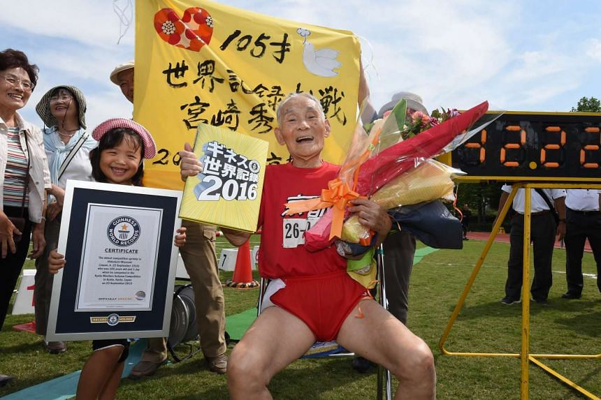 Hidekichi Miyazaki, 105, is congratulated by family members after setting a 100 metres world record in the over-105 age category.