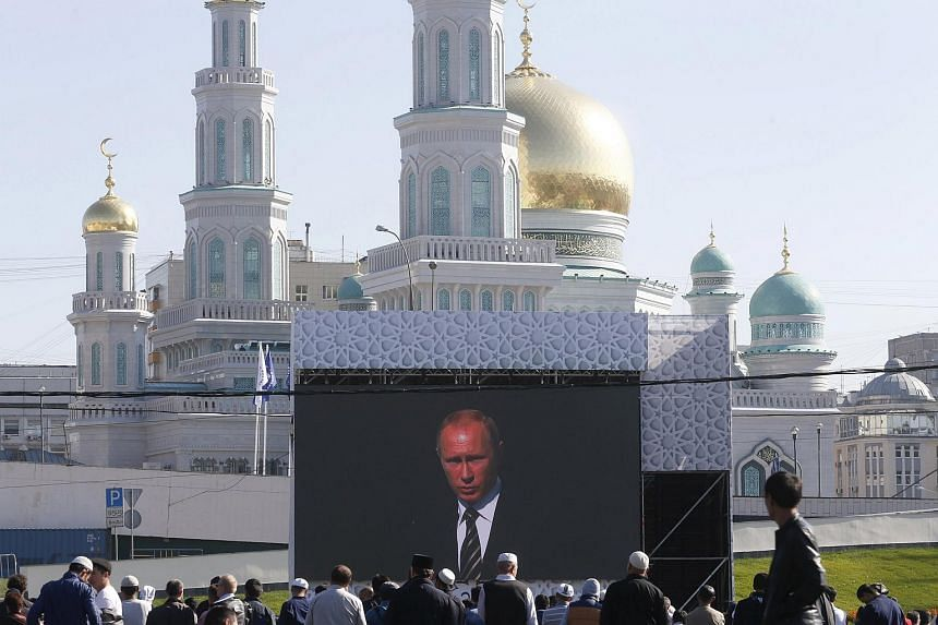 People listen to Russian President Vladimir Putin as he delivers a speech at a ceremony to open the Moscow Grand Mosque on Sept 23, 2015.