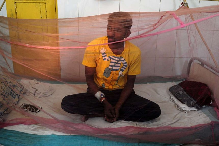An Indian man suspected to have dengue waits under a mosquito net in a dengue ward of a government hospital in Allahabad last week.