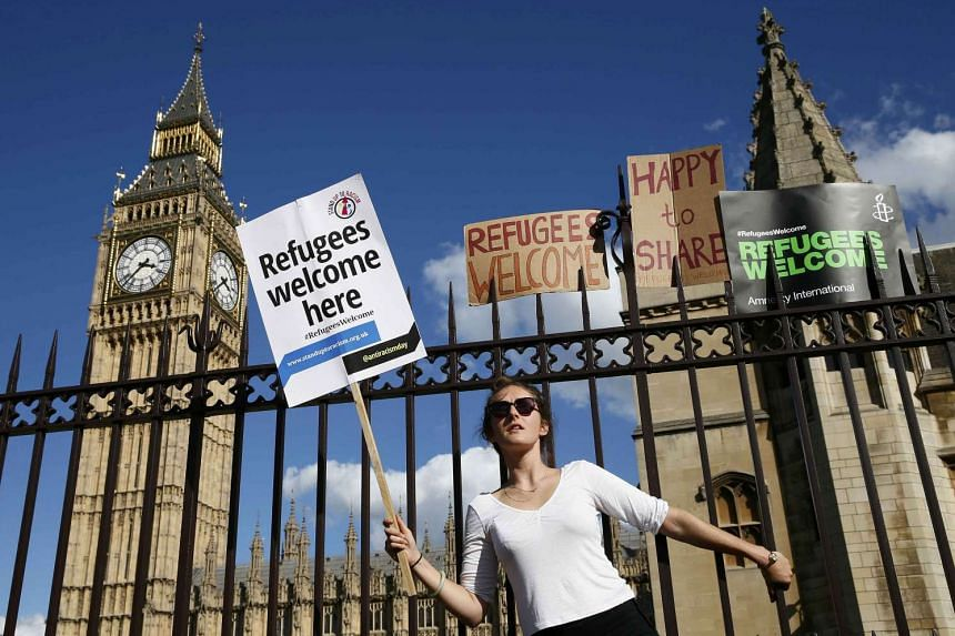 A protester holds on to the railings outside the Houses of Parliament in London during a demonstration to express solidarity with migrants.