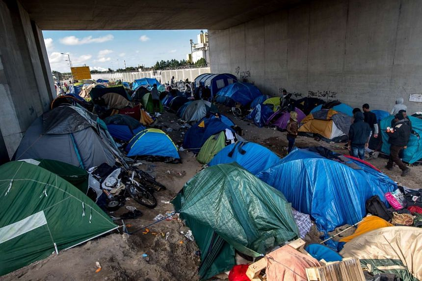 "Migrants camping under a bridge last Saturday at a site in Calais, France, dubbed the ""New Jungle"", where some 3,000 people have set up temporary shelter. Most of the migrants are trying desperately to get to England."