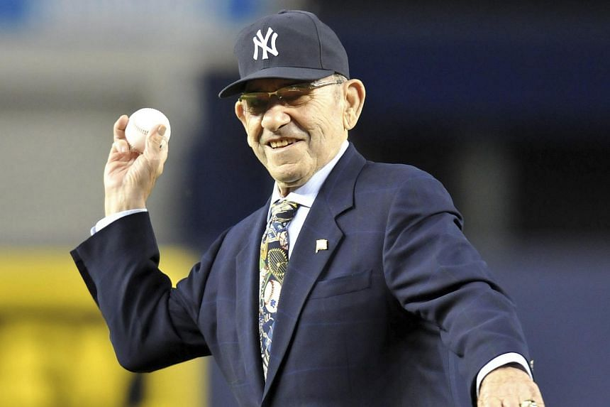 Baseball Hall of Famer and former New York Yankees catcher Yogi Berra throws out the ceremonial first pitch before the start of a game in this Oct 9, 2010 file photo.