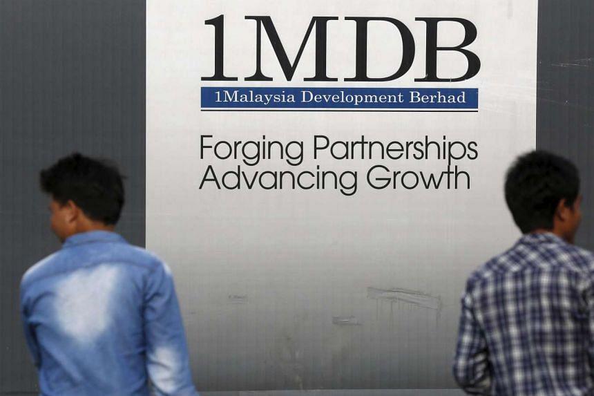 Men walk past a 1 Malaysia Development Berhad (1MDB) billboard at the funds flagship Tun Razak Exchange development in Kuala Lumpur, Malaysia.