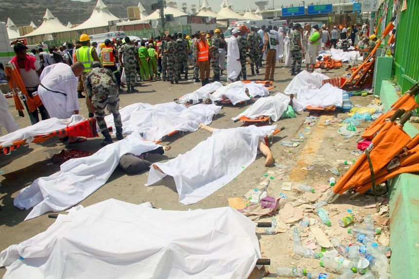 Saudi emergency personnel and Hajj pilgrims stand near bodies covered in sheets in Mina on Sept 24, 2015.