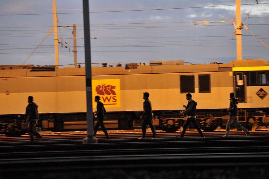 Migrants walking along the railway tracks of the Eurotunnel terminal at the Calais-Frethun station outside the northern French port of Calais on Aug 10, 2015. In July, Eurotunnel said 2,000 attempts a night were being made to get into the tunnel, bu