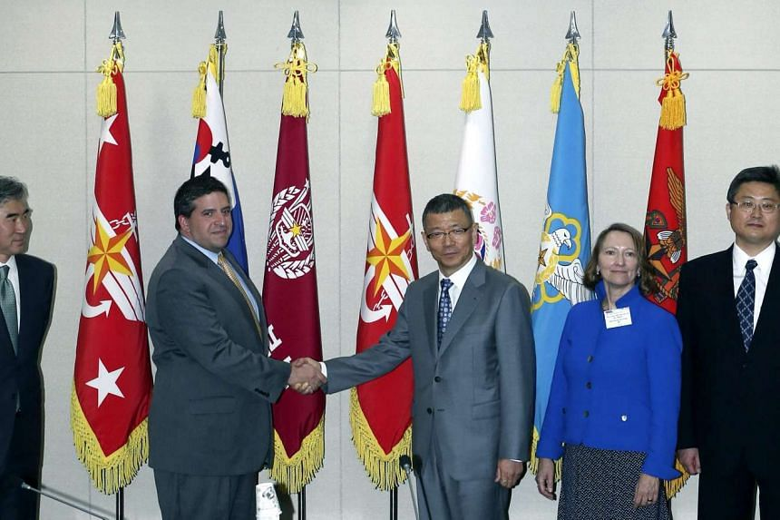 Yoo Jeh-seung (third from the right), deputy minister for policy at South Korea's Defense Ministry, shakes hands with Abraham Denmark (second from left), US deputy assistant secretary of defence for East Asia, prior to their talks at the defence mini