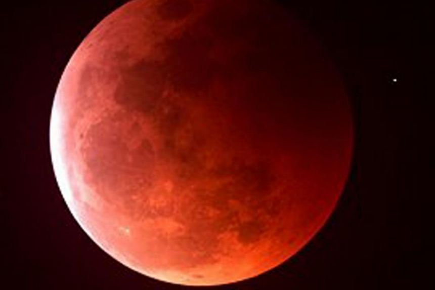 "A blood moon at mid-eclipse on June 15, 2011. Skygazers will be treated to a rare double spectacle of a swollen ""supermoon"" bathed in the blood-red light of a total eclipse on Sept 28, 2015."