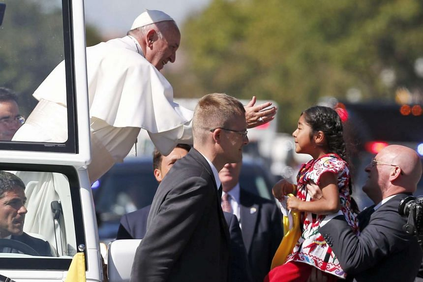 Pope Francis reaches from the Popemobile for a child that is brought to him during a parade in Washington DC, US, Sept 23, 2015. Pope Francis is on a five-day trip to the USA, which includes stops in Washington DC, New York and Philadelphia, after a