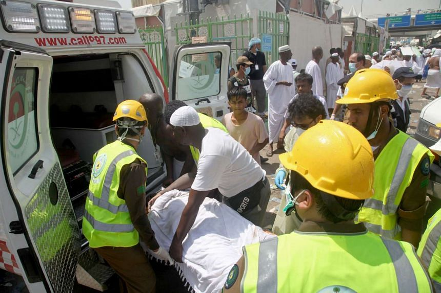 Saudi emergency personnel and Hajj pilgrims load a wounded person into an ambulance at the site where at least 450 were killed and hundreds wounded in a stampede in Mina on Sept 24, 2015.