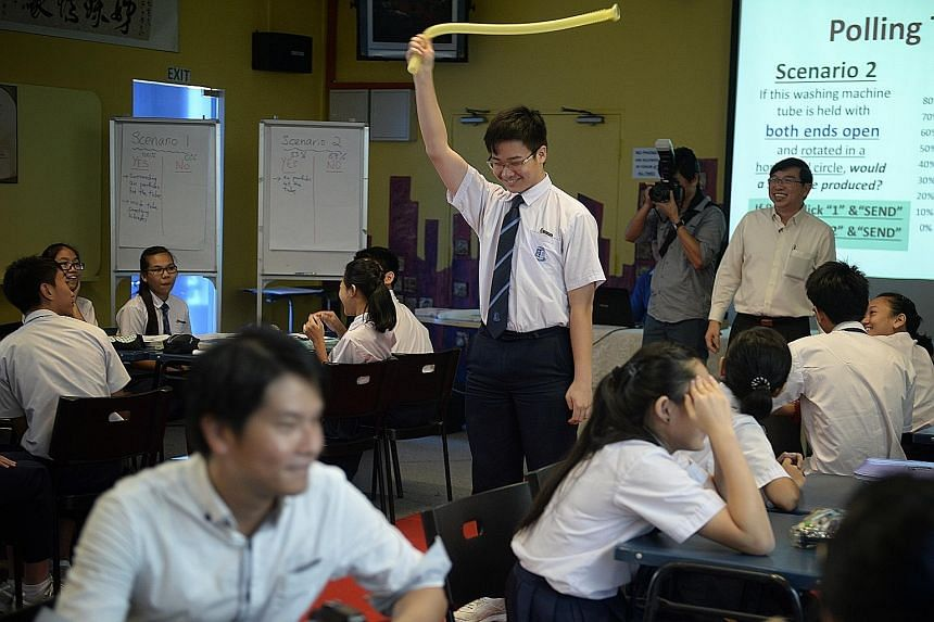 Fifteen-year-old Cai Bingfeng twirls a washing machine drainpipe during a demonstration class held yesterday at the newly set up Centre for Teaching and Learning Excellence at Yusof Ishak Secondary School.