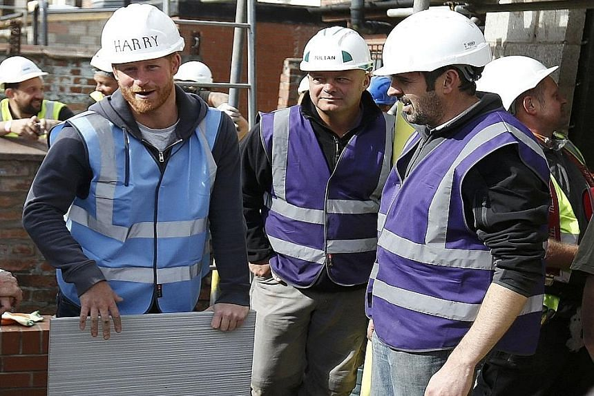 Britain's Prince Harry preparing to lay some paving slabs during a visit to Manchester yesterday. He and his brother, Prince William, have pitched in as part of the BBC television series DIY SOS, which turns several empty properties on a derelict str