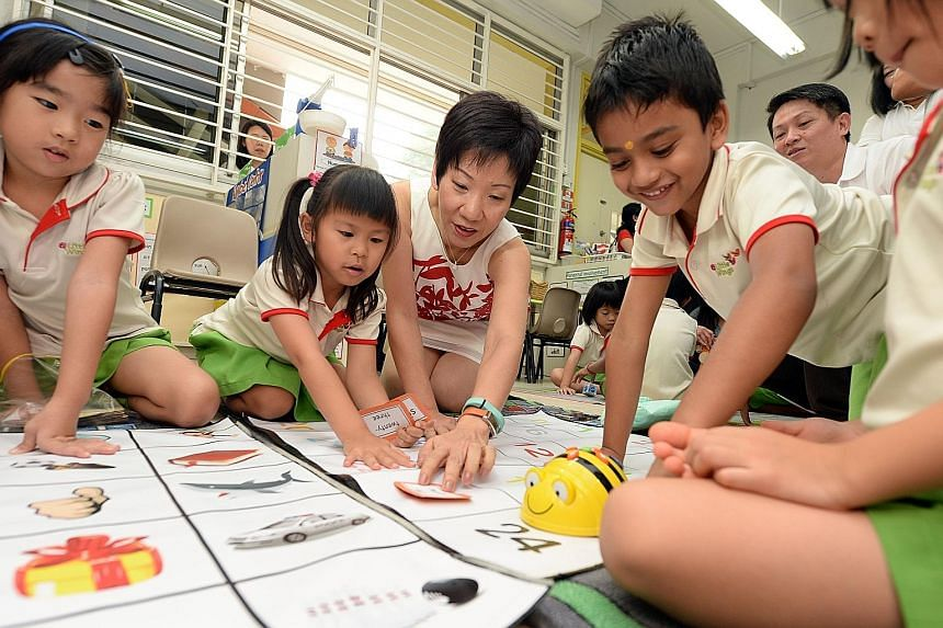 Ms Grace Fu, MP for Yuhua and Minister in the Prime Minister's Office, playing with the children at the PAP Community Foundation Sparkletots pre-school in Yuhua using the BeeBot teaching tool.