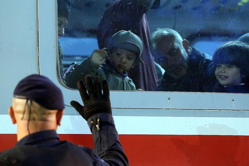 A police officer waving to migrant children on a train heading to the Croatian- Hungarian border at a station in Croatia's east.