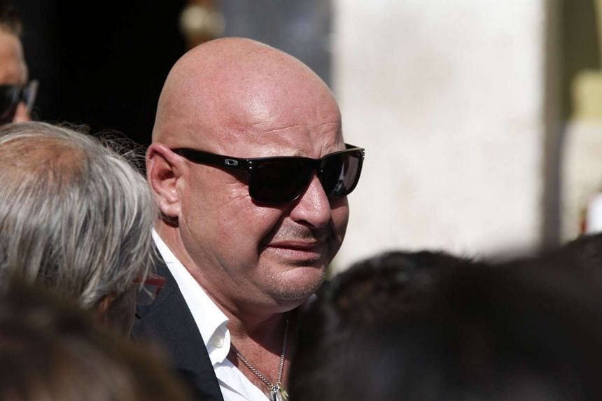 Philippe Bianchi, the father of late French Formula One driver Jules Bianchi, pays his last respect to his son's coffin after his funeral ceremony on July 21, 2015.