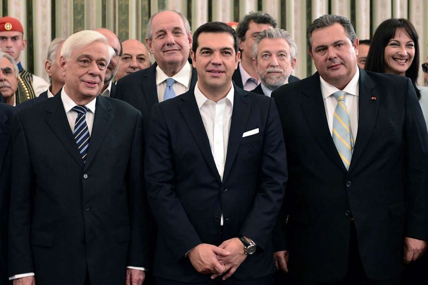 Greek PM Alexis Tsipras (centre) poses with Defence Minister Panos Kammenos of the Independent Greeks (right) and Greek President Prokopis Pavlopoulos (left) after the swearing-in ceremony of the new government.