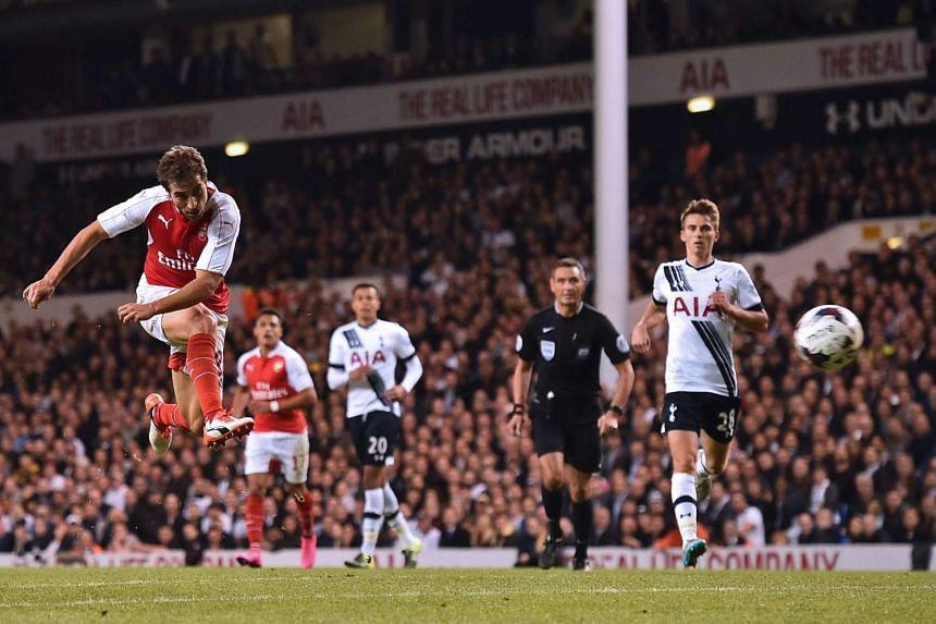 Arsenal's French midfielder Mathieu Flamini (left) shoots to score their seond goal.