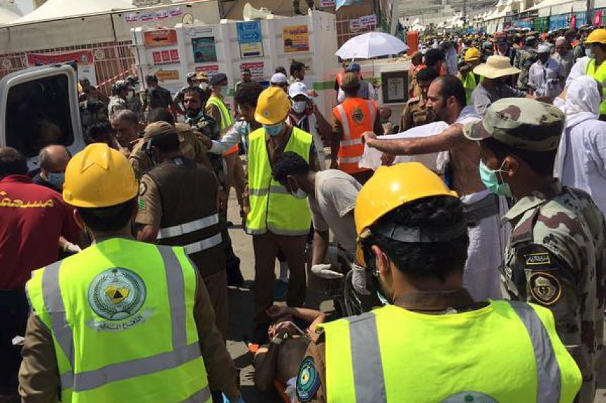 Saudi Civil Defense personnel attempting to help pilgrims, after a stampede occurred at Mina, outside the Muslim holy city of Mecca, in this handout picture published on the Twitter account of the Directorate of the Saudi Civil Defense.