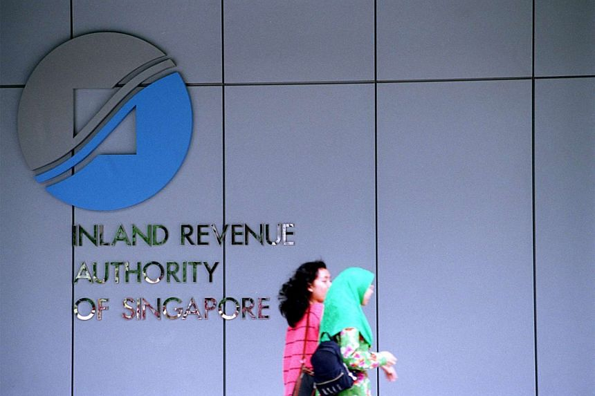 Two passers-by walk pass the logo of Inland Revenue Authority of Singapore (IRAS) at Revenue House in 1998.