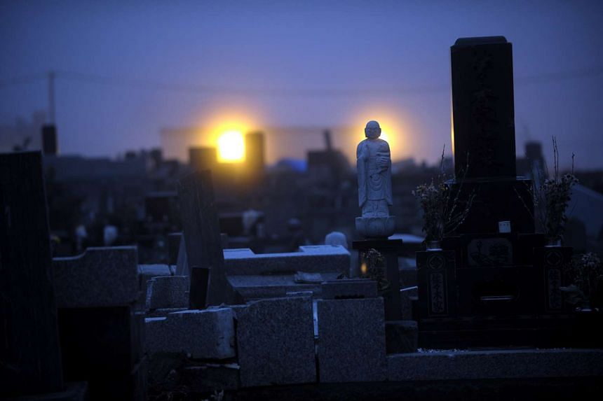 As dusk falls on Ishinomaki, Miyagi Prefecture, street lamps illuminate a graveyard outside a temple that is packed with toppled headstones which are mostly damaged and strewn haphazardly against one another.