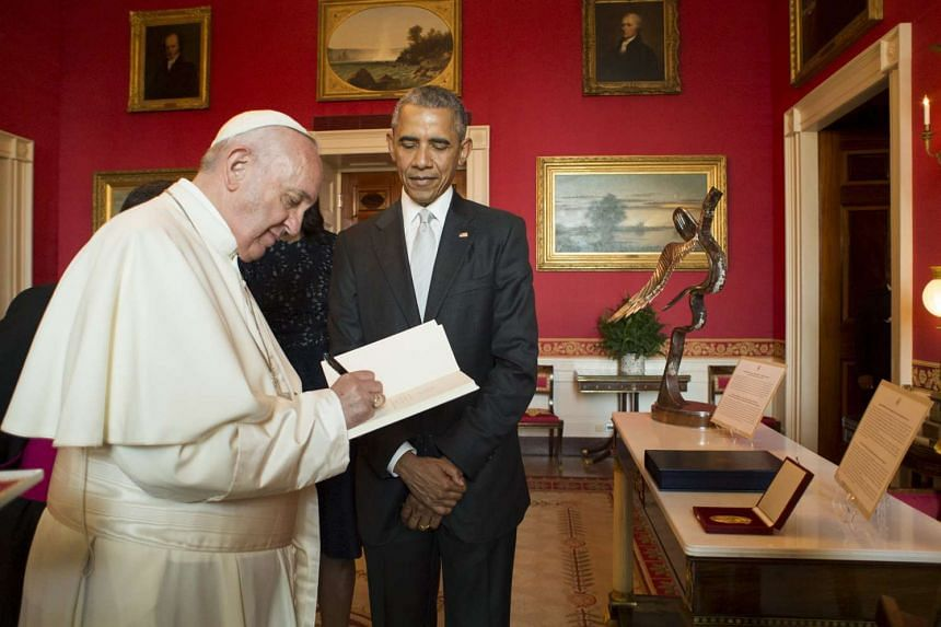 US President Barack Obama looks on as Pope Francis signs a Papal encyclical in the Oval Office during ceremonies welcoming the pontiff to the White House in Washington on Sept 23, 2015.