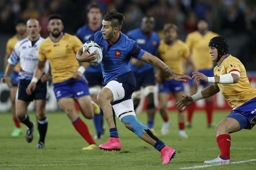 France's wing Sofiane Guitoune (left) runs with the ball in front of Romania's wing Adrian Apostol (right).
