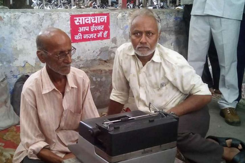 Indian street typist Kishan Kumar (left) with his new typewriter on a street in Lucknow on Tuesday. He was presented with the new machine after his old one was destroyed by a policeman in an image that went viral.
