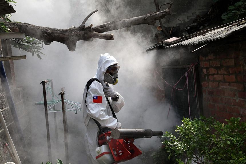 A chemical warfare soldier fumigating an alley in Tainan City, southern Taiwan, on Sept 22, 2015.