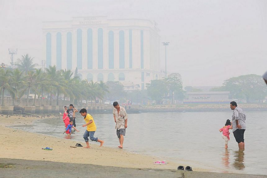 Parents and children enjoying a dip by the sea at Stulang, Johor Baru during the Hari Raya Aidiladha and school holiday break despite the haze on Sept 24, 2015.