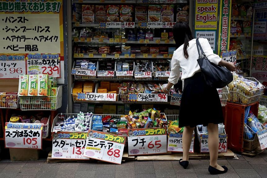 A shopper looks at items outside a discount store at a shopping district in Tokyo, Japan.